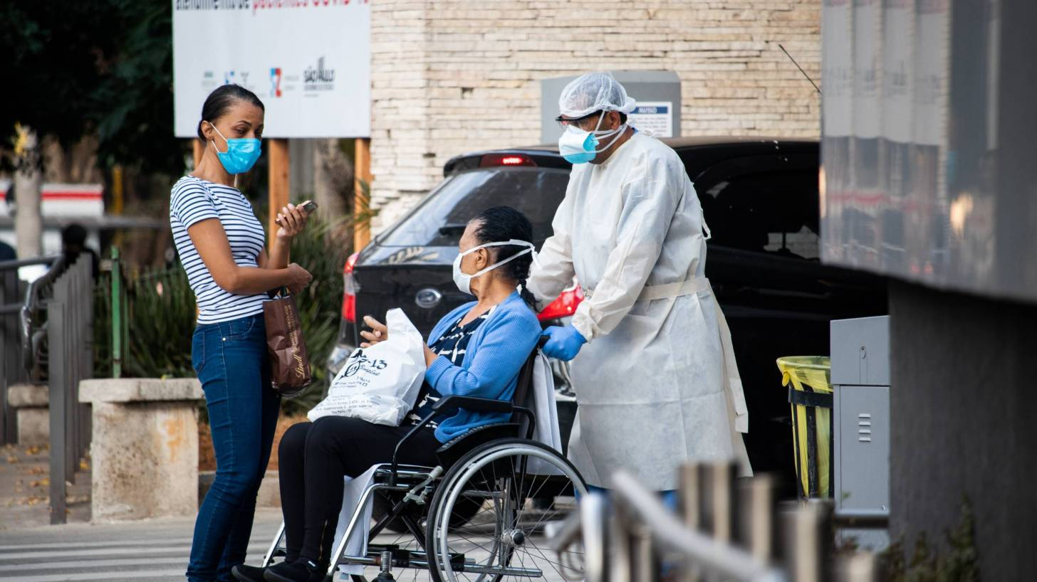 person being wheeled out of the hospital after recovering from COVID-19