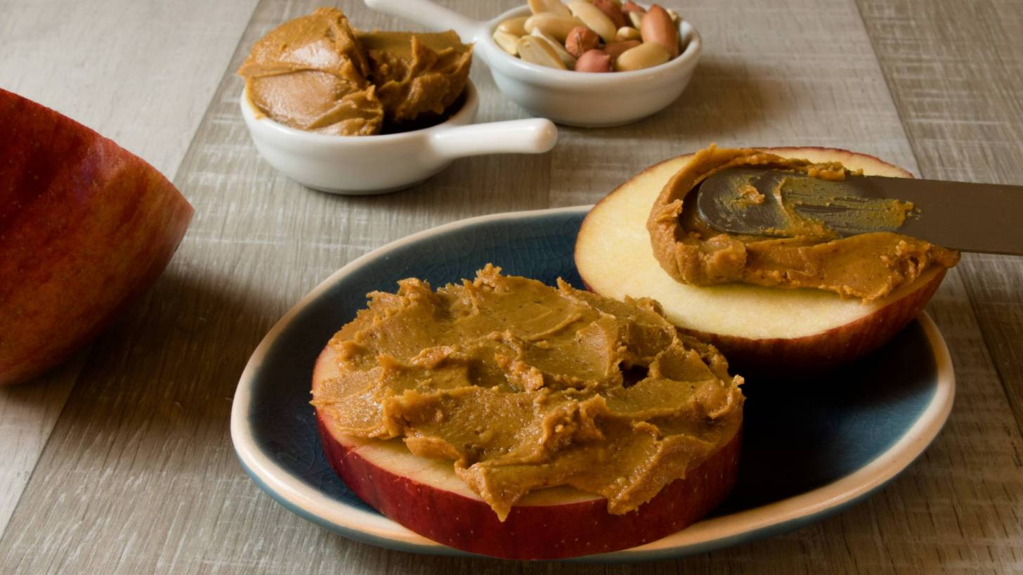 peanuts, and peanut butter spread on an apple