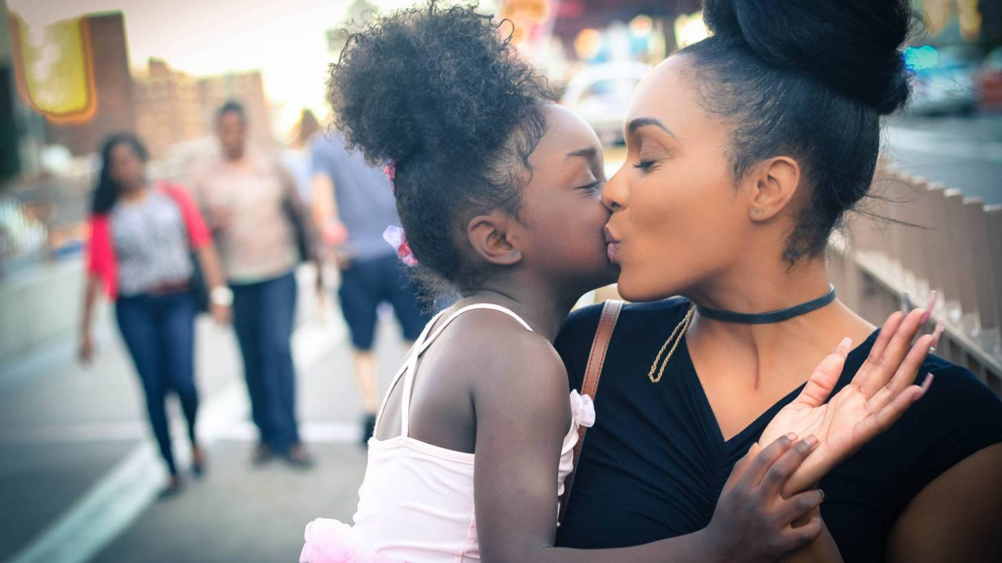mom and daughter sharing a kiss