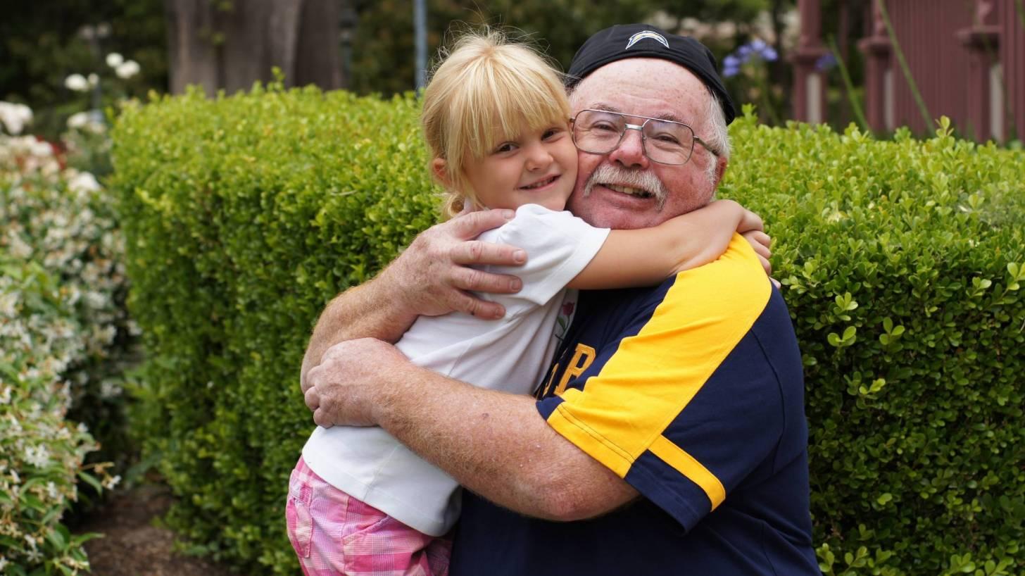 happy healthy grandpa hugging his grand daughter