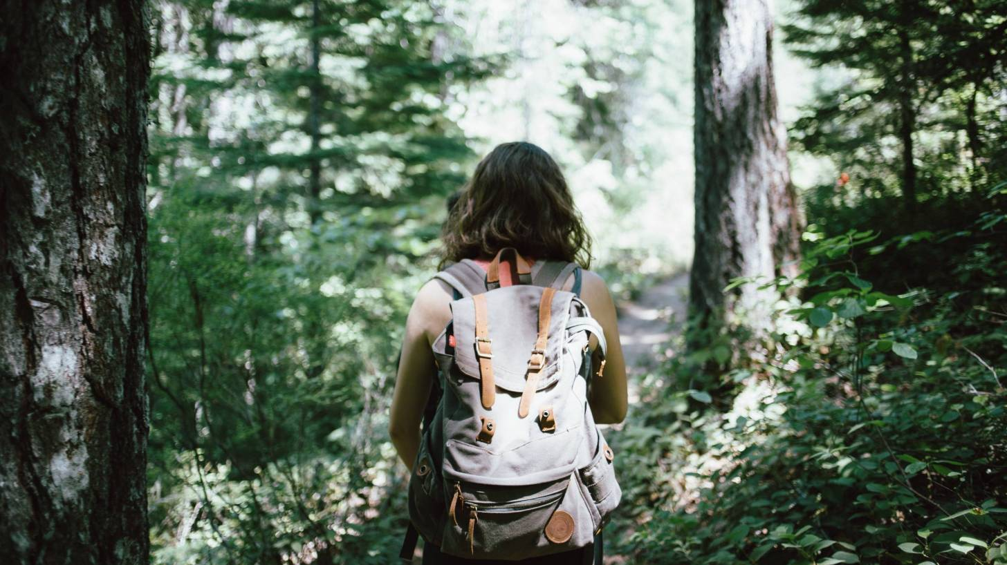 young girl in woods hiking