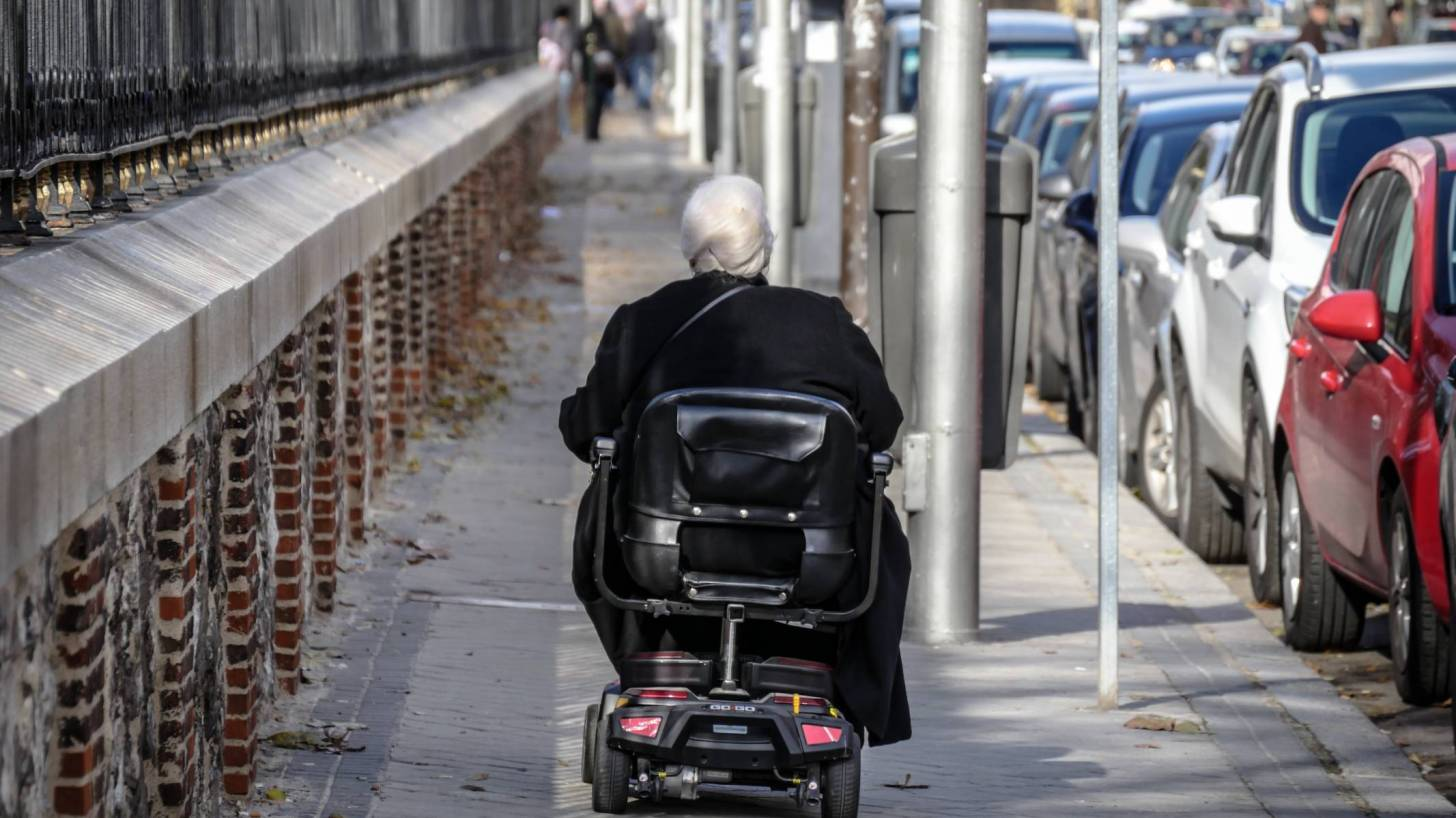 person in wheel chair going down a side walk