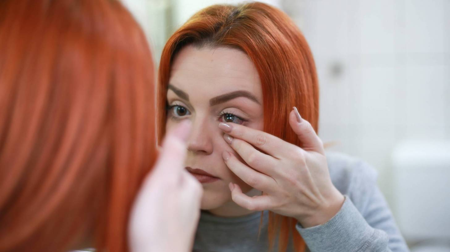 woman putting contact lens in her eyes