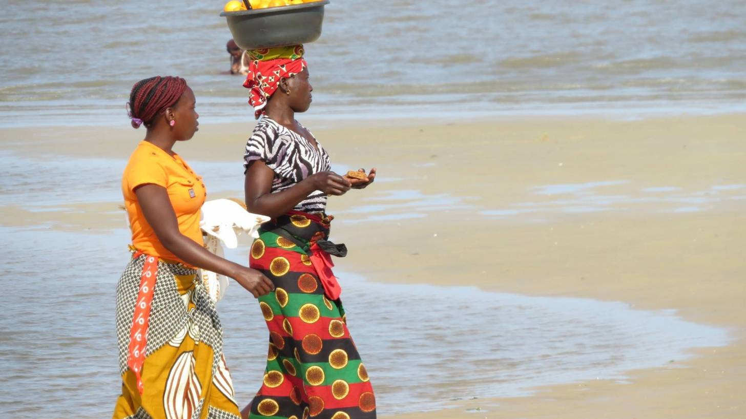 african women walknig carrying food on their head in baskets