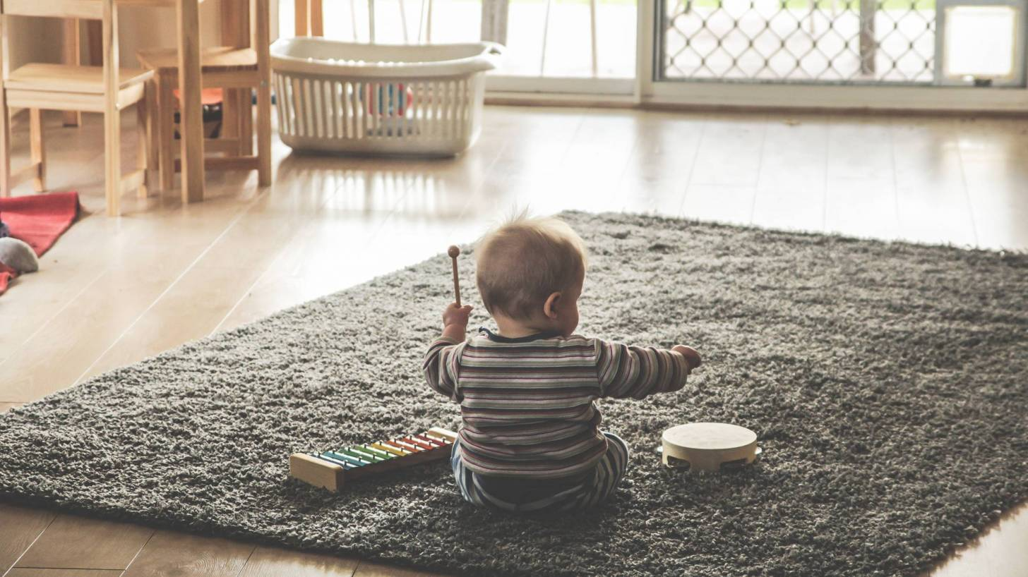 toddler on the floor playing with musical instruments