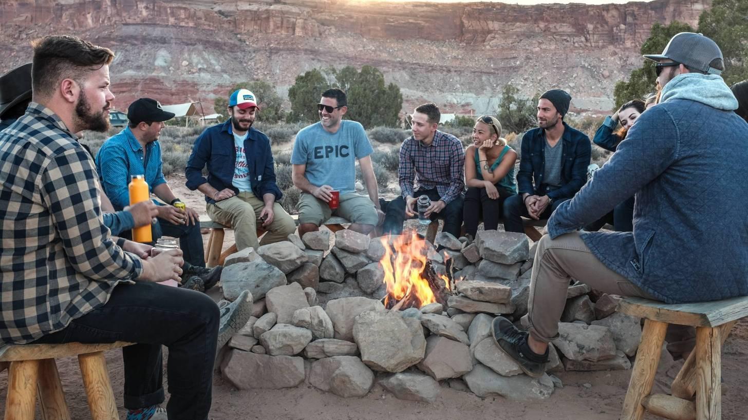 men sitting around an outdoor fire pit