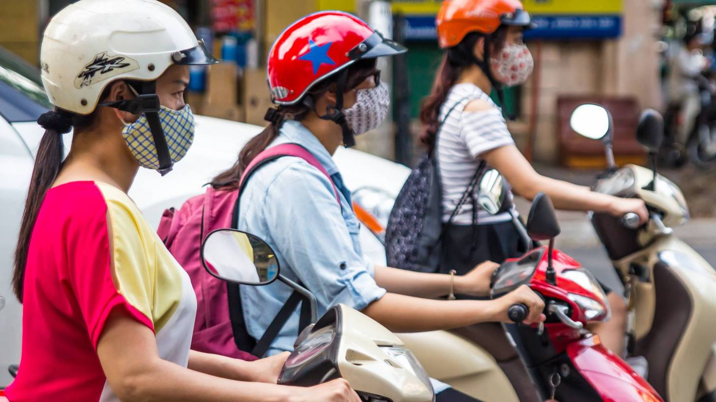 girls on scooters with masks and helmets
