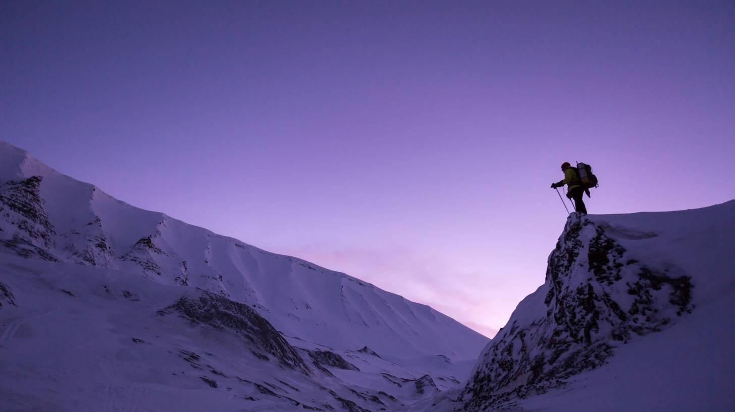 man on cliff snow skiing