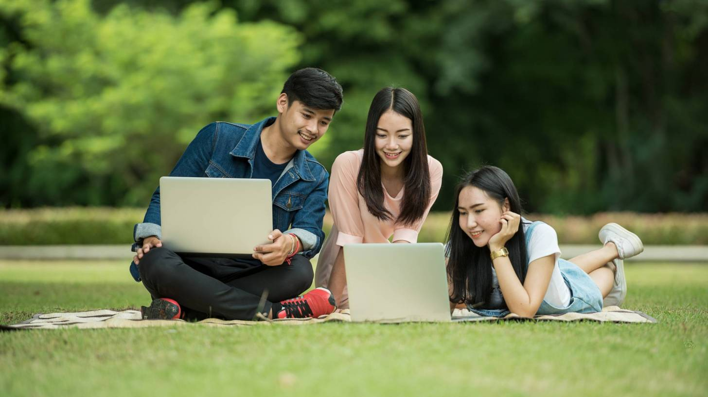 young adults studying on lawn