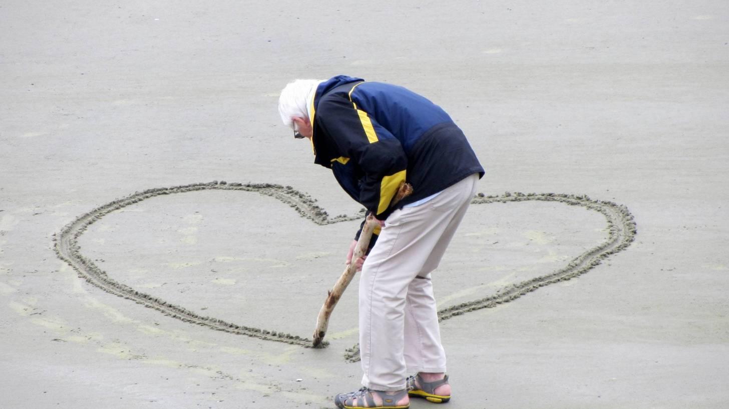 older man drawing a heart on beach