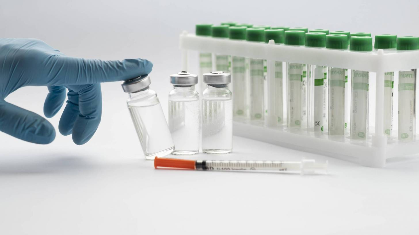 gloved hand pointing to three vials of vaccine
