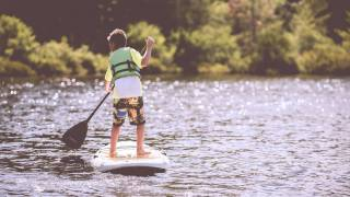 boy paddle boarding on a lake