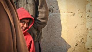 young boy hiding behind his parent