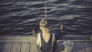 young boy fishing off the end of a dock