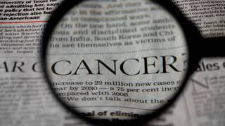 newspaper headline with cancer magnified