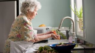 older woman in kitchen washing veggies