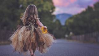 young girl in make believe dress running down the road