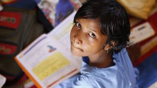 young indian girl studying, looking up at the camera