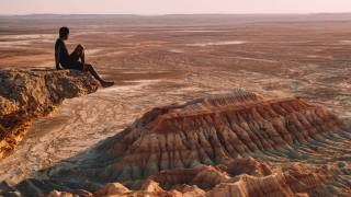 man sitting on a cliff overlooking the desert