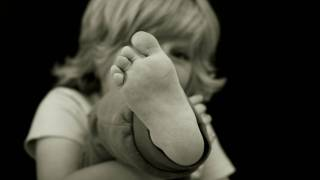 young boy holding up his foot