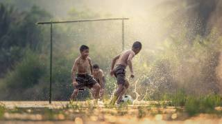 young boys playing soccer in muddy field