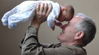 grandpa with his new grand baby protected from pertussis
