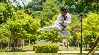 karate student high in the air, kicking