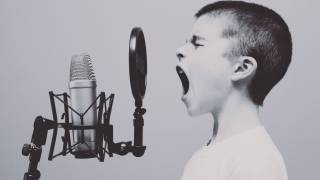 young boy yelling into an old fashion microphone
