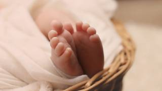 new born baby feet in a basket