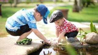 two boys playing in a water pond