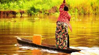 woman on river trading in africa