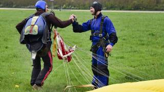 parachutists shaking hands after landing