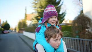 little sister riding on her borthers shoulders happy dressed warm