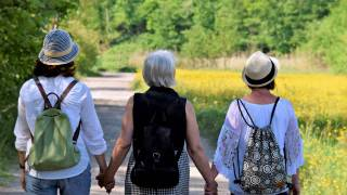 women holding hands looking hopeful