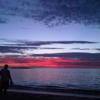 sun setting on beach couple walkiing