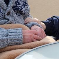 older person in nursing home being taken care