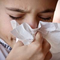 young boy sneezing into a tissue