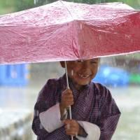 cute little boy holding umbrella in the rain