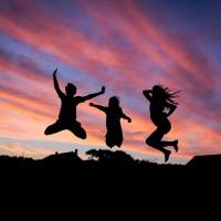 three people jumping up in the sun set happy