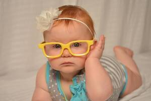 happy healthy little girl with yellow glass frames on