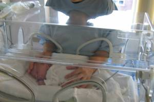 preterm baby in an incuboator mom holding inside