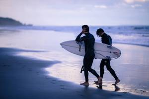 men going surfing at dusk