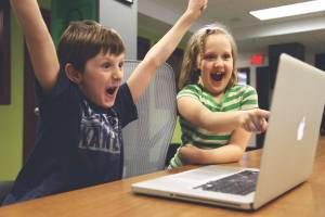 children happy looking at a computer screen