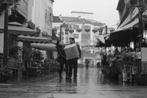 chinese couple carrying a heavy box