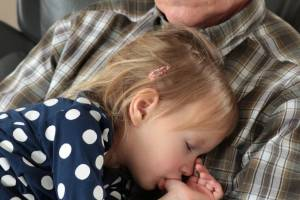 grandpa holding a sleeping grandchild