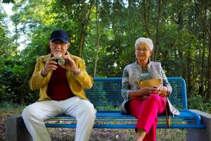 grandparents sitting on a bench taking photos