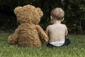 toddler sitting on ground with Teddy bear