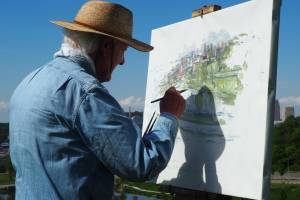 older man painting on a canvas outside