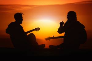 two people playing the guitar at sunset