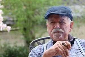 older man enjoying a cigar outside